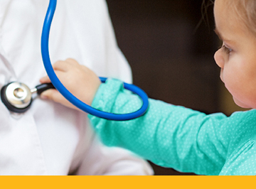 young child playing with stethoscope