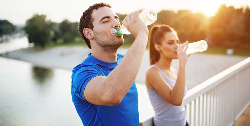 man and woman drinking a bottle of water after working out