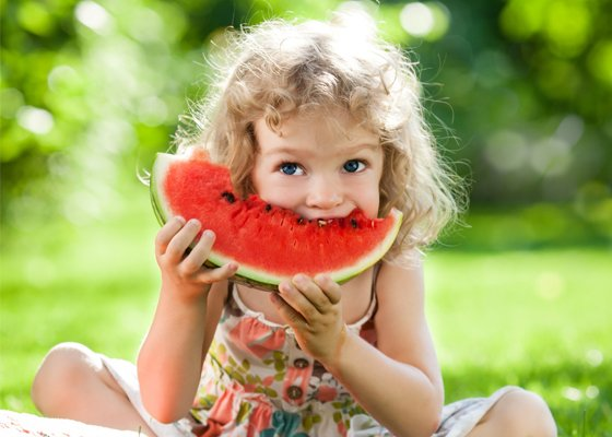 Young girl eating taking a bite of watermelon
