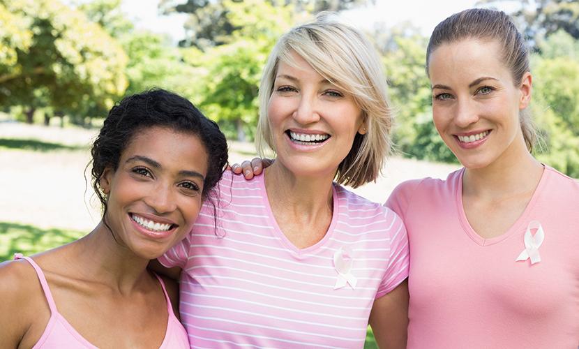 3 smiling women wearing pink