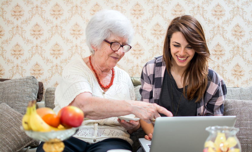 Young woman on computer sitting next to grandmother