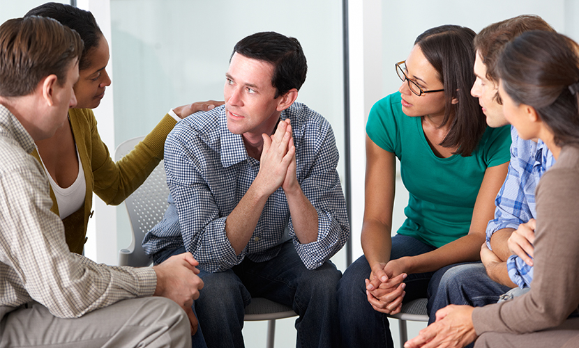 Young adults sitting in a circle consoling a member of the support group