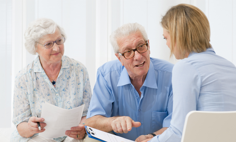elderly couple asking advice from group leader