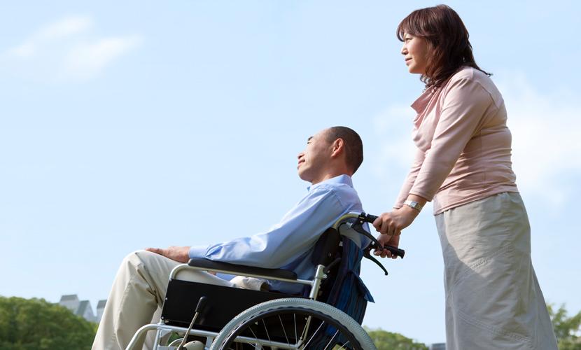 woman pushing man in wheelchair