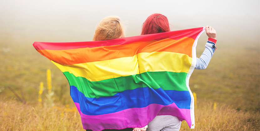 2 females holding LGBT rainbow flag