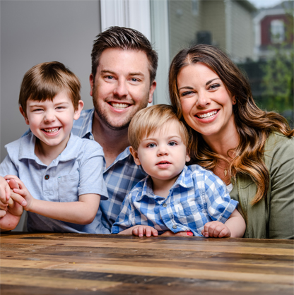 Husband and wife with 2 young sons smiling in family portrait