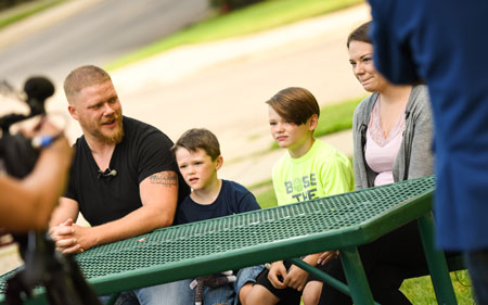 family sitting on picnic table