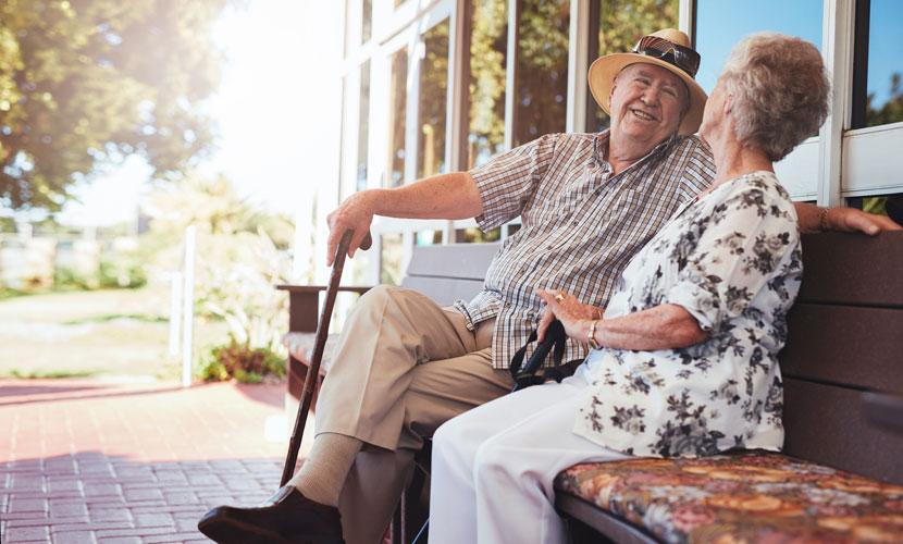happy elderly couple sitting on bench