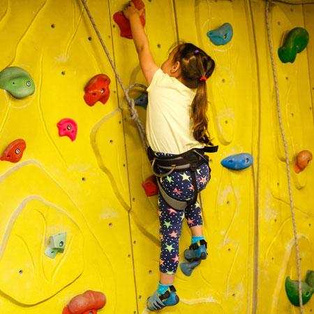 girl on yellow climbing wall