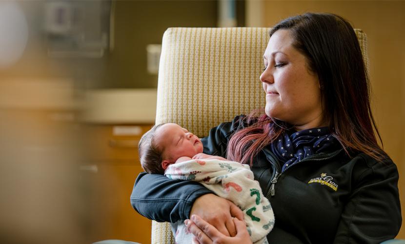 maple grove hospital nurse holding newborn baby