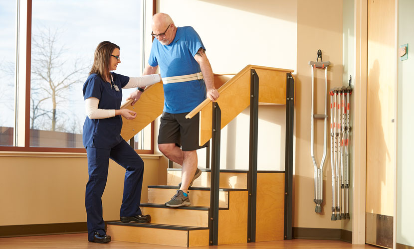 woman assisting injured man down stairs