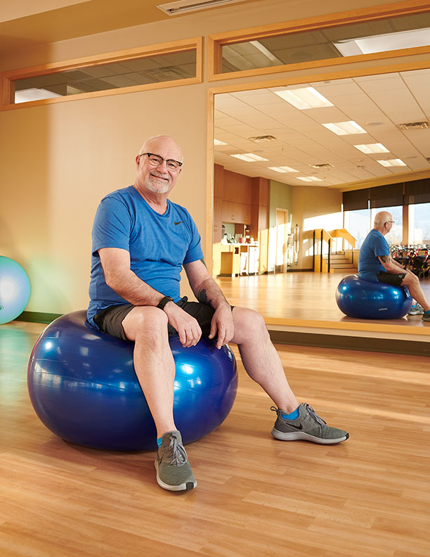 man on exercise ball smiling