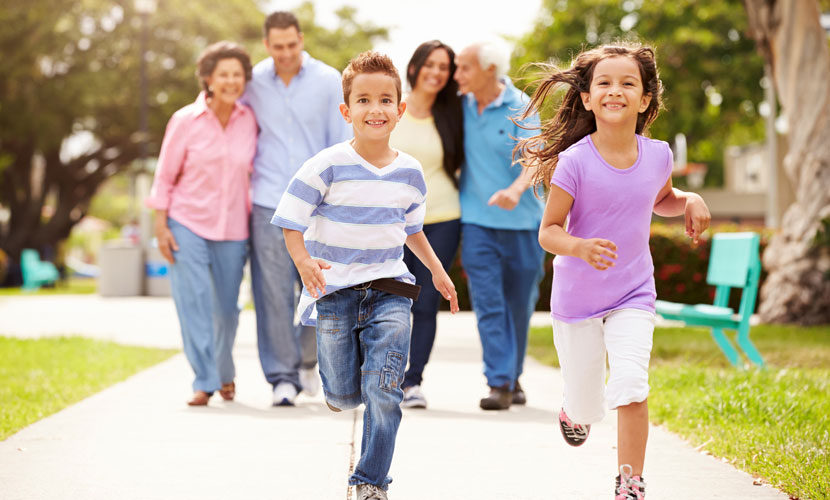 kids running ahead of parents and grandparents on sidewalk