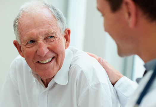 elderly man smiling with doctor