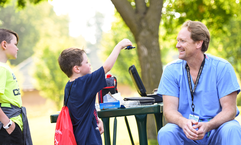 two boys with doctor on picnic table