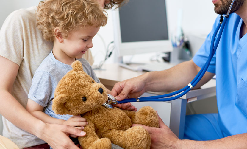 doctor with stethoscope on teddy bear with kid