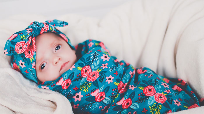 baby in headband and swaddle