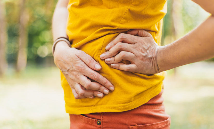person in yellow shirt with hip pain