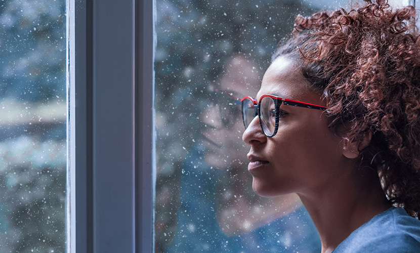 Sad african american woman looking out of the window
