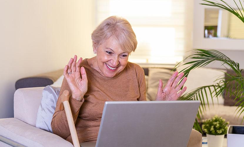 elderly woman on computer waving